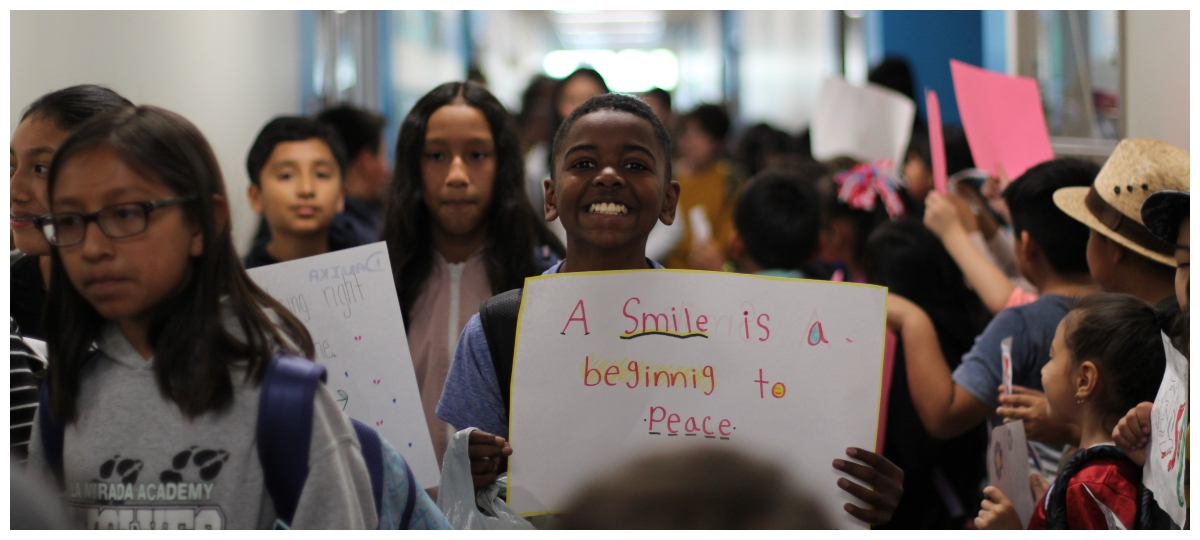 Kindness week, student holding a sign saying a smile is a beginning to peace.